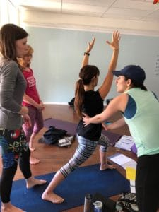 Instructor teaching yoga teacher training students how to make adjustments