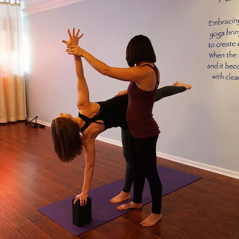 Photo of a yoga instructor helping a student in a pose.