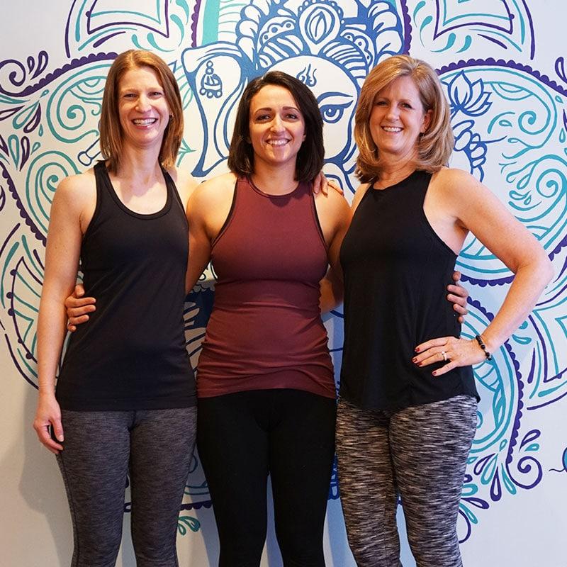 Photo of three smiling yoga instructors in a yoga studio
