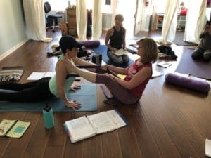 Yoga teacher training student learning how to do adjustments
